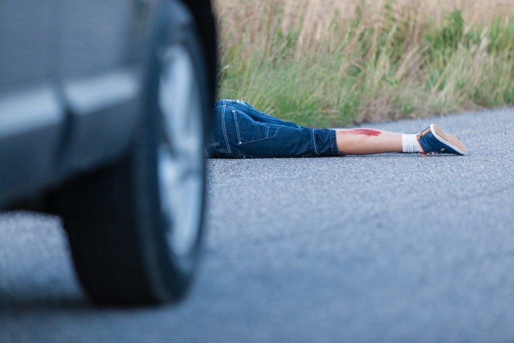Boy hit by a car and lying behind the vehicle