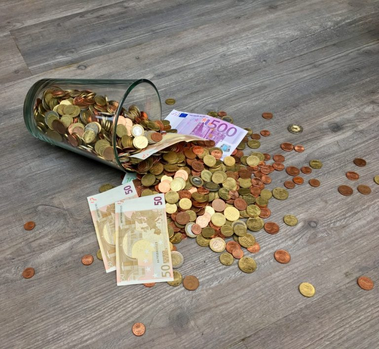 coins and bills in a glass toppled over